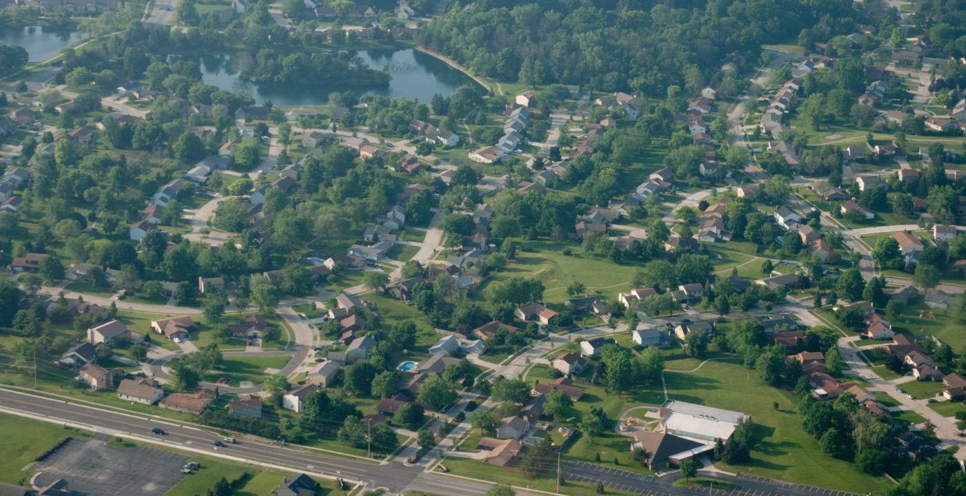 View of the suburbs in a midwest American town from an aerial view. Traditional tree-lined streets and green summer grass.